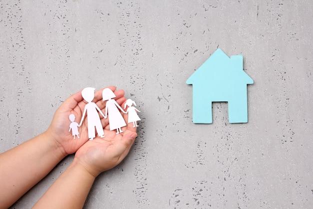 Mulher com as mãos segurando um recorte de família de papel, casa de família em fundo cinza no estúdio.