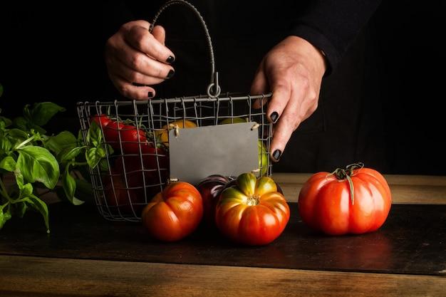 Mulher com as mãos segurando um wirebasket com tomates