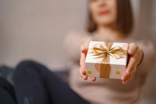 Mulher com as mãos segurando uma caixa branca embrulhada com laço dourado, foco na caixa