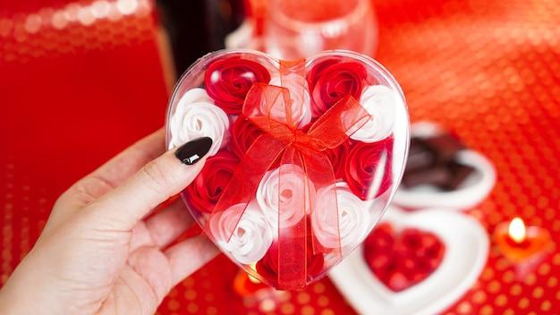 Mulher com as mãos segurando uma caixa de presente em forma de coração com lindas rosas sobre vermelho festivo. conceito de dar um presente nos feriados do dia dos namorados