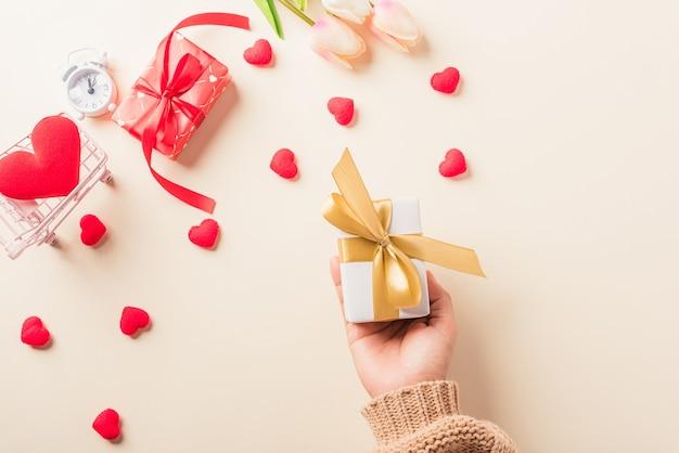 Mulher com as mãos segurando uma caixa de presente ou presente decorada e um coração vermelho surpresa