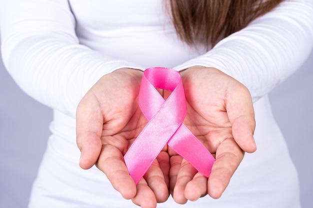 Mulher com as mãos segurando uma fita rosa de conscientização do câncer de mama.