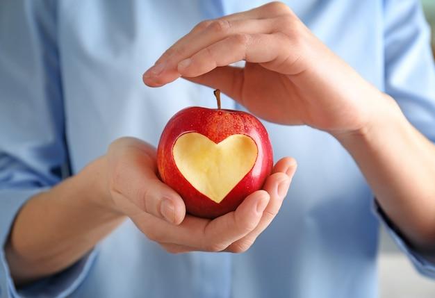 Mulher com as mãos segurando uma maçã vermelha fresca com recorte em forma de coração, close-up