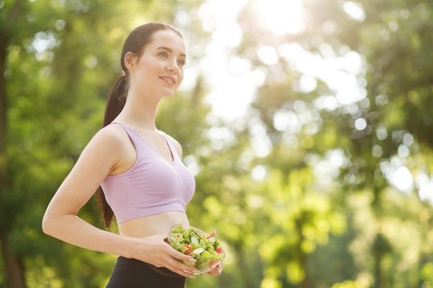 Mulher com as mãos segurando uma salada fresca de verão com vegetais crus, pepinos, tomates, alface na tigela.