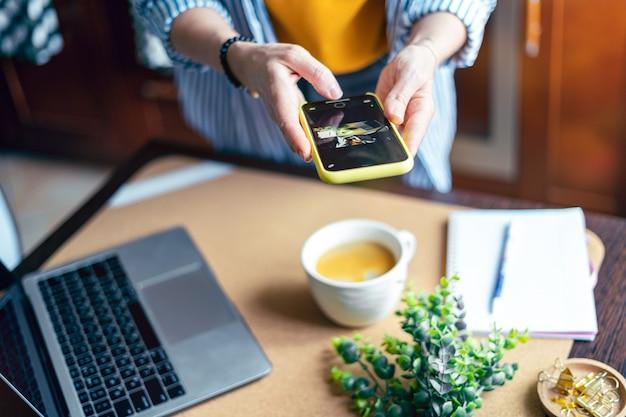 Mulher com as mãos tirando foto de folhas verdes de xícara de café e café da manhã em casa na cozinha marrom no