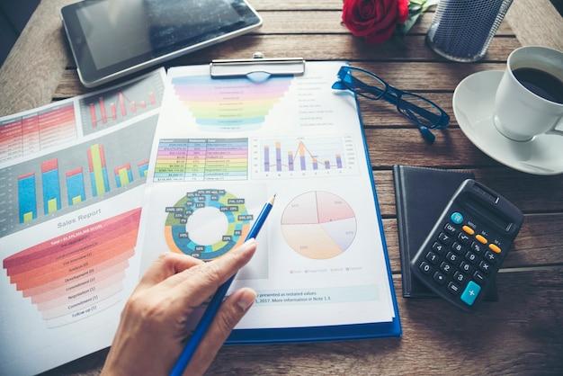 Mulher com as mãos trabalhando escritório laptop negócios documento financeiro gráfico e gráfico na mesa xícara de café