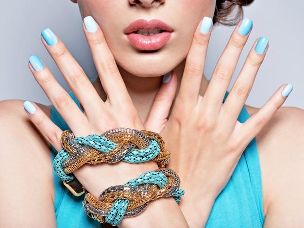 Mulher com as mãos unhas manicure joias da moda azul.
