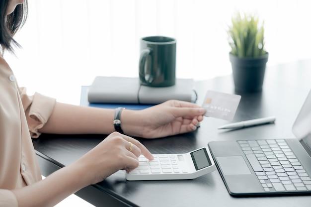 Mulher com as mãos usando a calculadora e segurando o cartão de crédito enquanto está sentada à mesa