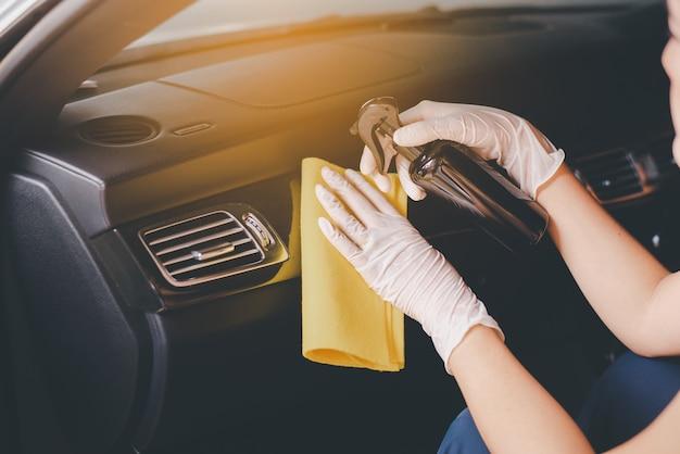 Mulher com as mãos usando um pano para limpar o carro. segurança e proteção contra infecção durante a pandemia do vírus covid19