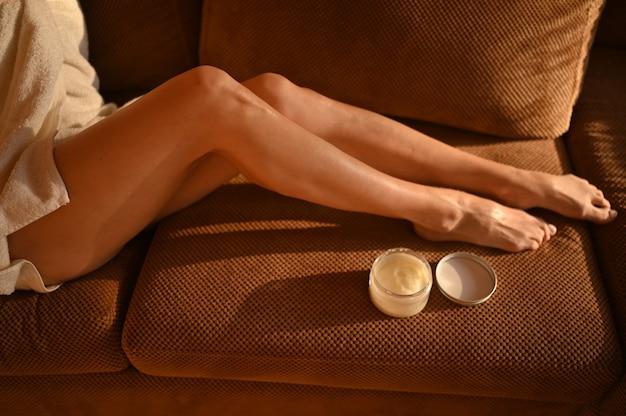 Mulher com as pernas nuas sentada no sofá em casa em um dia ensolarado
