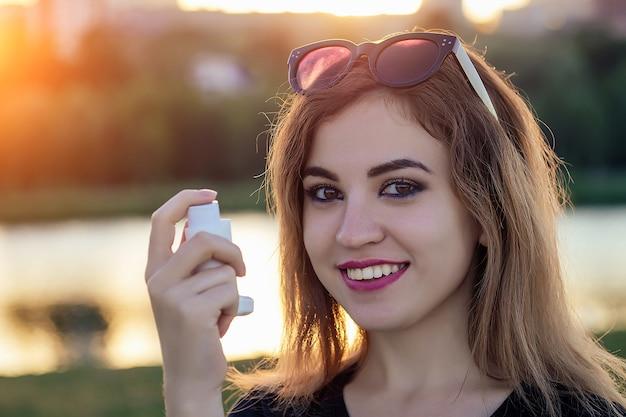 Mulher com asma em um parque de verão segurando um inalador
