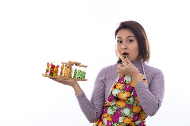 Mulher com avental colorido segurando garrafas de doces