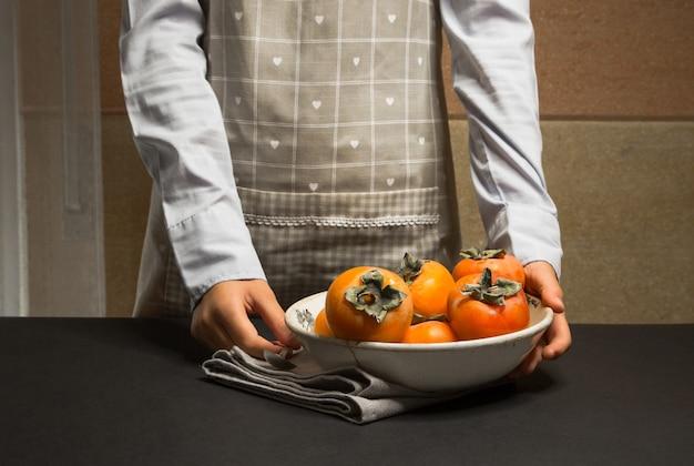 Mulher com avental de cozinha com prato de caqui