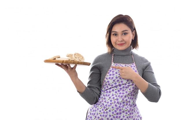 Mulher com avental roxo segurando cookies