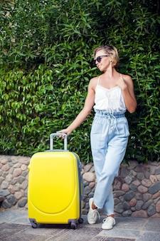 Mulher com bagagem ao ar livre. conceito de viagens, férias e estilo de vida