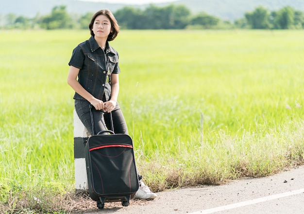 Mulher, com, bagagem, boleia, ao longo, um, estrada
