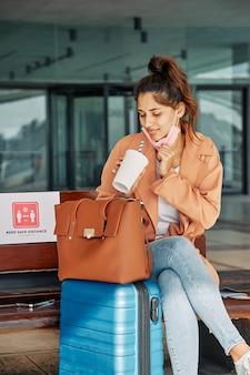 Mulher com bagagem e bolsa no aeroporto durante a pandemia
