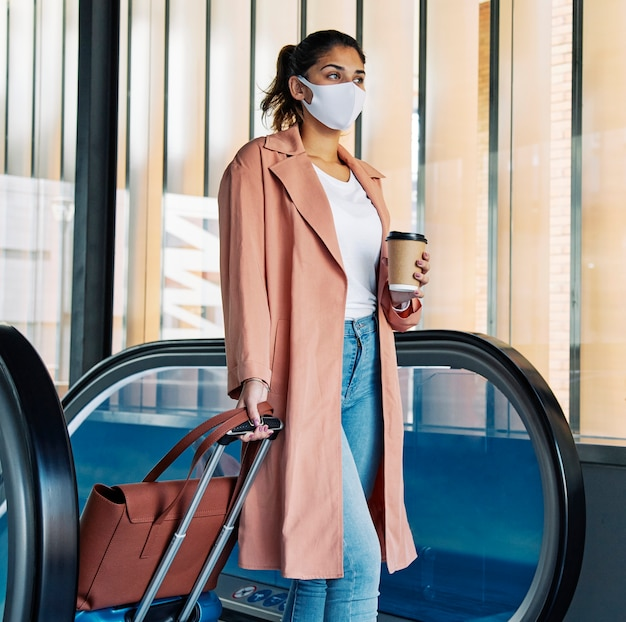 Mulher com bagagem e máscara médica no aeroporto durante a pandemia
