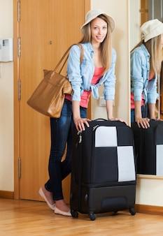 Mulher com bagagem perto da porta