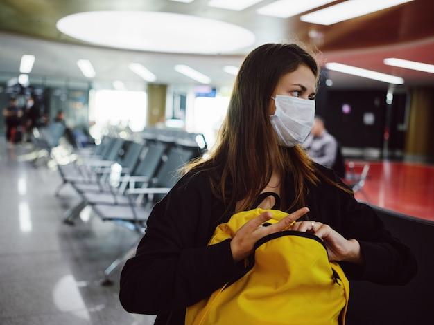 Mulher com bagagem sentada no aeroporto esperando o atraso de um voo