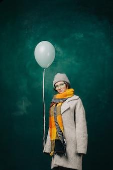 Mulher com balão nas mãos e roupas de inverno