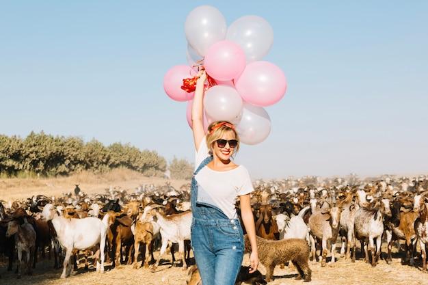 Mulher com balões andando perto de cabras