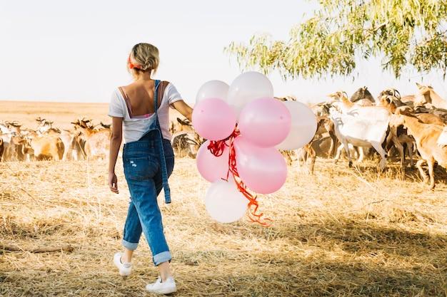 Mulher com balões andando perto do rebanho de cabras