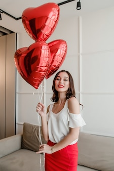 Mulher com balões em forma de coração, sorrindo e feliz em casa