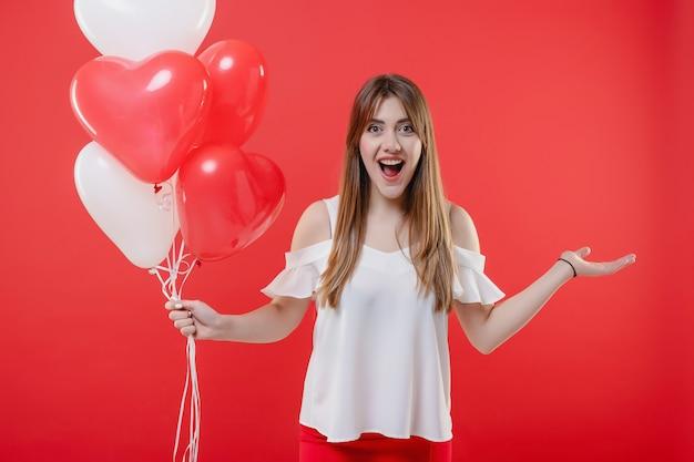 Mulher com balões em forma de coração sorrindo isolado sobre o vermelho