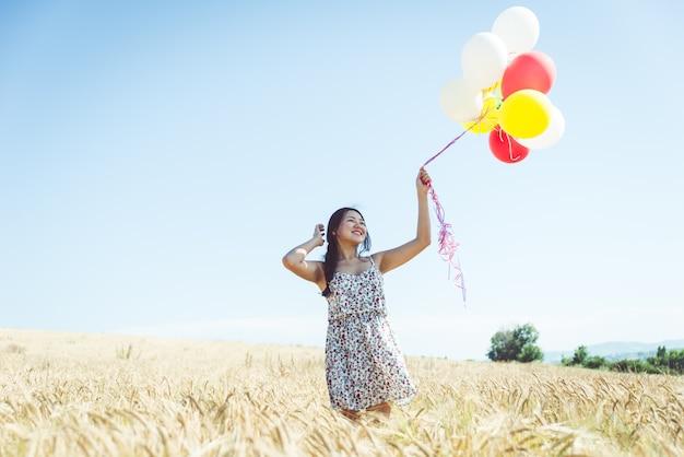 Mulher com balões em um campo de trigo