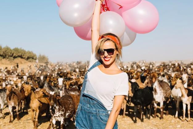 Mulher com balões na frente do rebanho