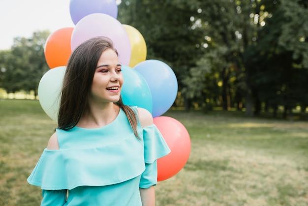 Mulher com balões olhando para longe