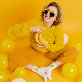 Mulher com bananas e balões amarelos