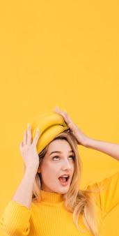 Mulher com bananas na cabeça dela