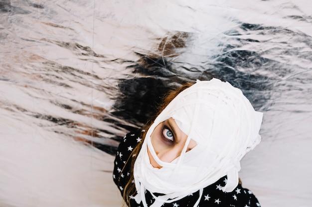 Mulher com bandagem por parede de folha