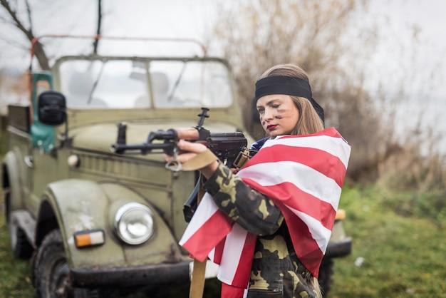 Mulher com bandeira americana e rifle perto de carro militar