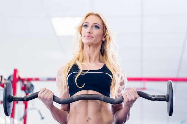 Mulher, com, barbell, fazendo, desporto, em, ginásio aptidão