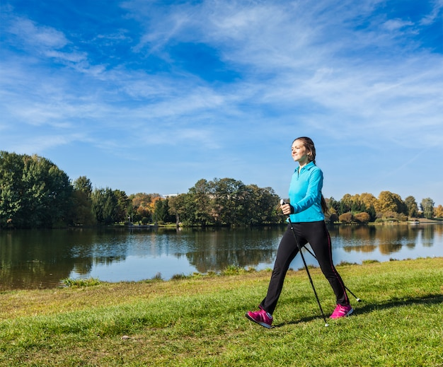 Mulher com bastões nórdicos no parque
