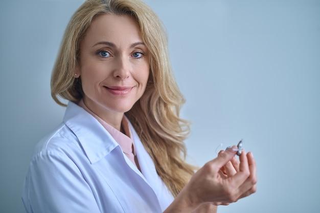 Mulher com bata médica mostrando aparelho auditivo