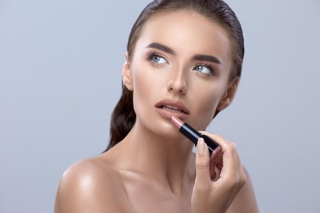 Mulher com batom, beleza closeup com batom, linda mulher aplicando batom e olhando para cima, linda garota aplicando maquiagem