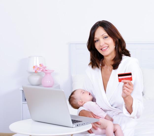 Mulher com bebê, cartão de crédito e laptop em casa