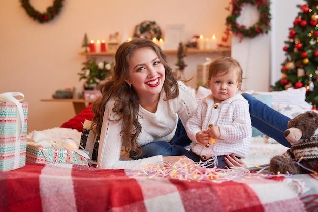 Mulher com bebê na cozinha decorada para o natal.