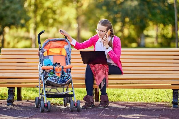 Mulher com bebê no carrinho falando ao telefone ao ar livre