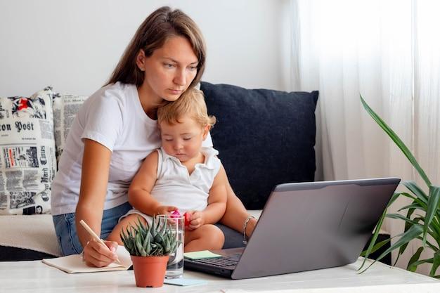Mulher com bebê trabalhando em um laptop de casa