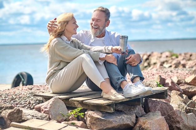 Mulher com bebida e homem rindo sentado ao ar livre