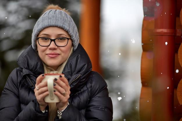 Mulher com bebida quente no dia de inverno