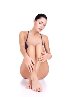 Mulher com belas pernas de biquíni sentada no fundo branco