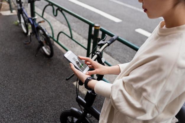 Mulher com bicicleta elétrica na cidade usando smartphone