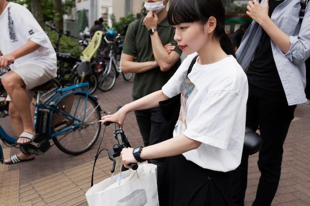 Mulher com bicicleta elétrica na cidade