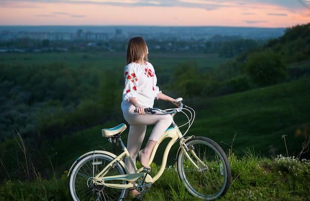 Mulher com bicicleta retro na colina à noite
